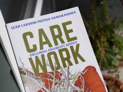 A copy of the book, Care Work. Cover art is an illustrated Brown body intertwined with a tree with many branches.